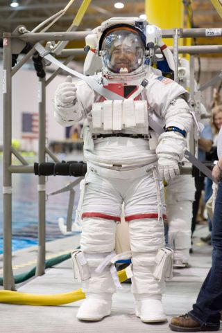 Dressed in a training version of his Extravehicular Mobility Unit spacesuit, Japan Aerospace Exploration Agency (JAXA) astronaut Satoshi Furukawa, Expedition 28/29 flight engineer, is about to be submerged in the waters of the Neutral Buoyancy Laboratory