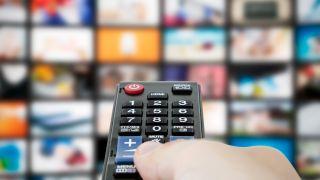Eine TV-Fernbedienung, die auf einen Bildschirm mit verschwommenen TV-Bannern zeigt