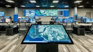 The Real-Time Intelligence Center in Lee County, FL, monitors public safety data. A centrally located touchscreen allows for collaboration of county assets (land, air and sea) to provide real-time, predictive, modern policing.