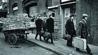 The Rolling Stones walking past a market trader down a Soho street carrying suitcases.