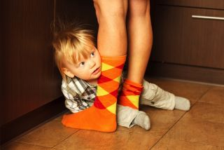 Shy toddler hiding behind mom's legs