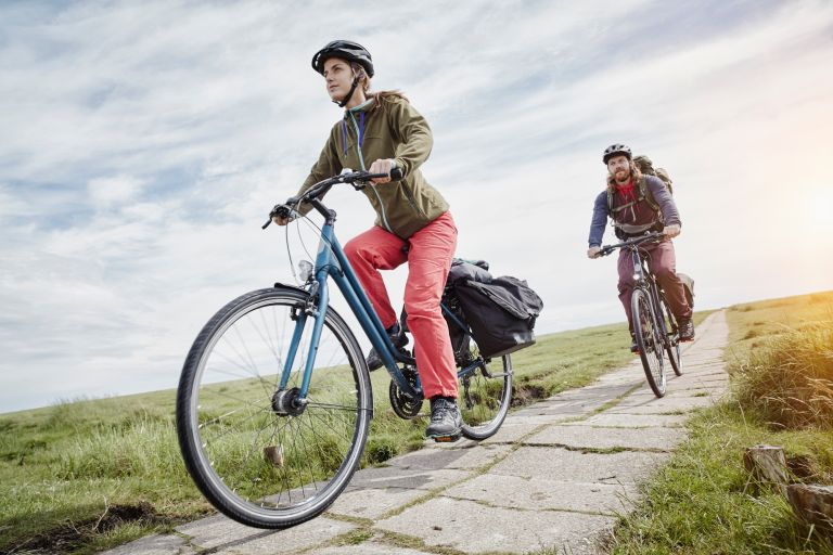 Best women's hybrid bike main image is of a women riding a bike on a path between two fields with man on a hybrid bike behind her