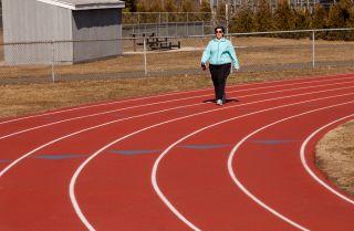 An overweight woman walks around a track.