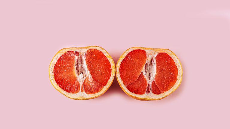 grapefruit cut in half on pink background