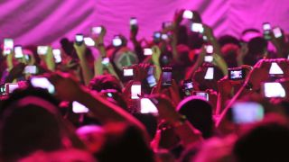 A photograph of lots of people using their phones at a gig