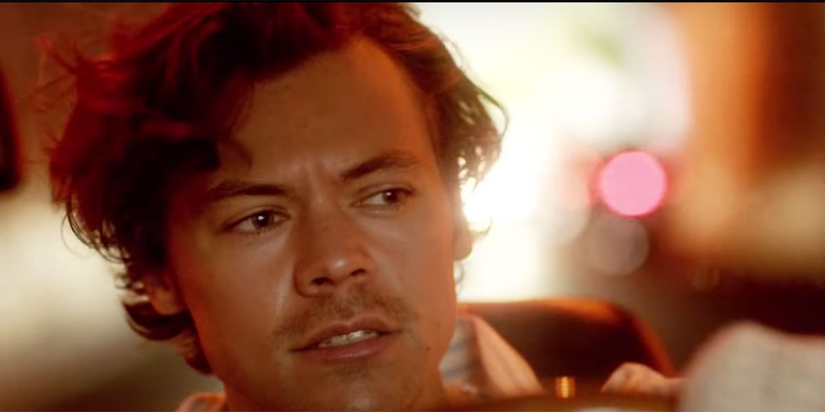 Harry Styles driving a car with cool lighting.