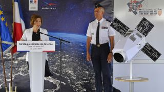 French Minister of Defense Florence Parly (left) discusses the new French space force in a speech at Airbase 942 in Lyon-Mont Verdun, on July 25, 2019. Next to her on stage, French Air Force general Philippe Lavigne stands beside a model of a satellite.