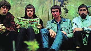John Mayall's Bluesbreakers sitting against a wall, Eric Clapton reading a copy of the Beano comic.