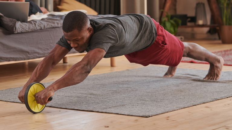 Man uses an ab roller to workout at home