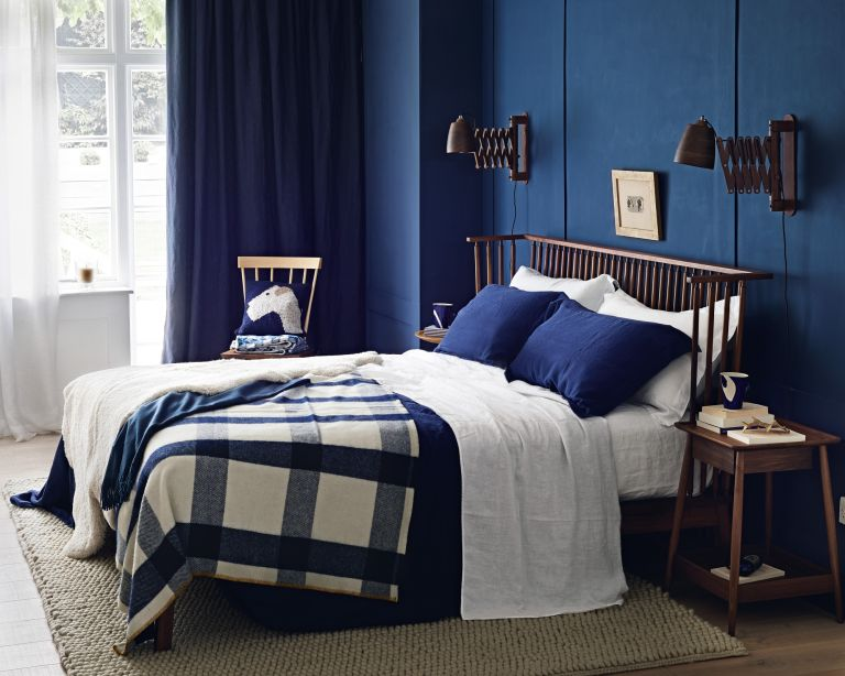 A bedroom with navy blue wall, brown wooden bed and white and navy bed linen
