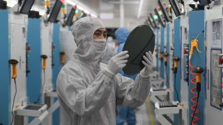 Employees work on the production line of silicon wafer at a factory in Jiaxing City, China