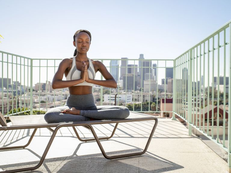 Young woman meditating with city in background, best meditation apps