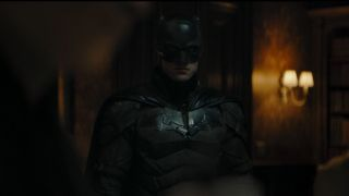 Batman (Robert Pattinson) approaches Commissioner Gordon in The Batman (2021)
