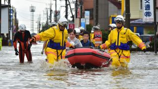Rescue workers transport people in a rubber boat in Oyama in Tochigi prefecture, north of Tokyo on Sept. 10, 2015, just after torrential rains flooded rivers and triggered landslides.