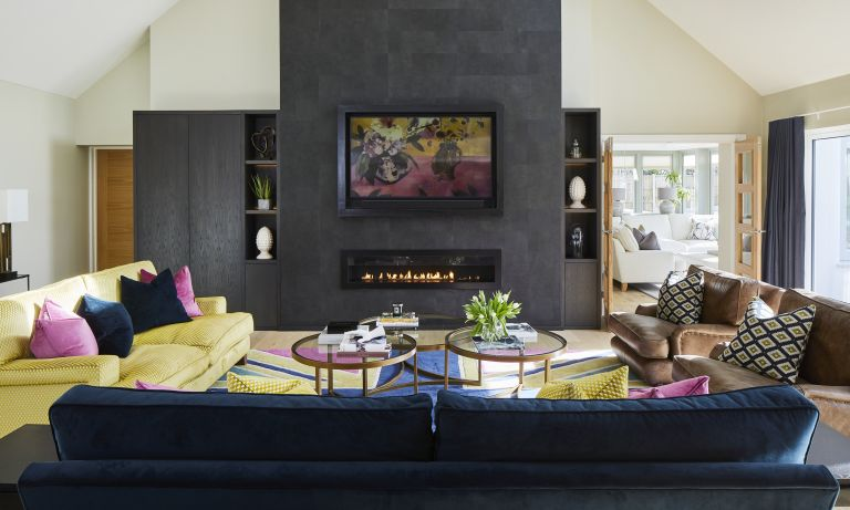 TV mounting ideas Yellow, grey and pink living room with leather sofa and TV mounted onto the wall