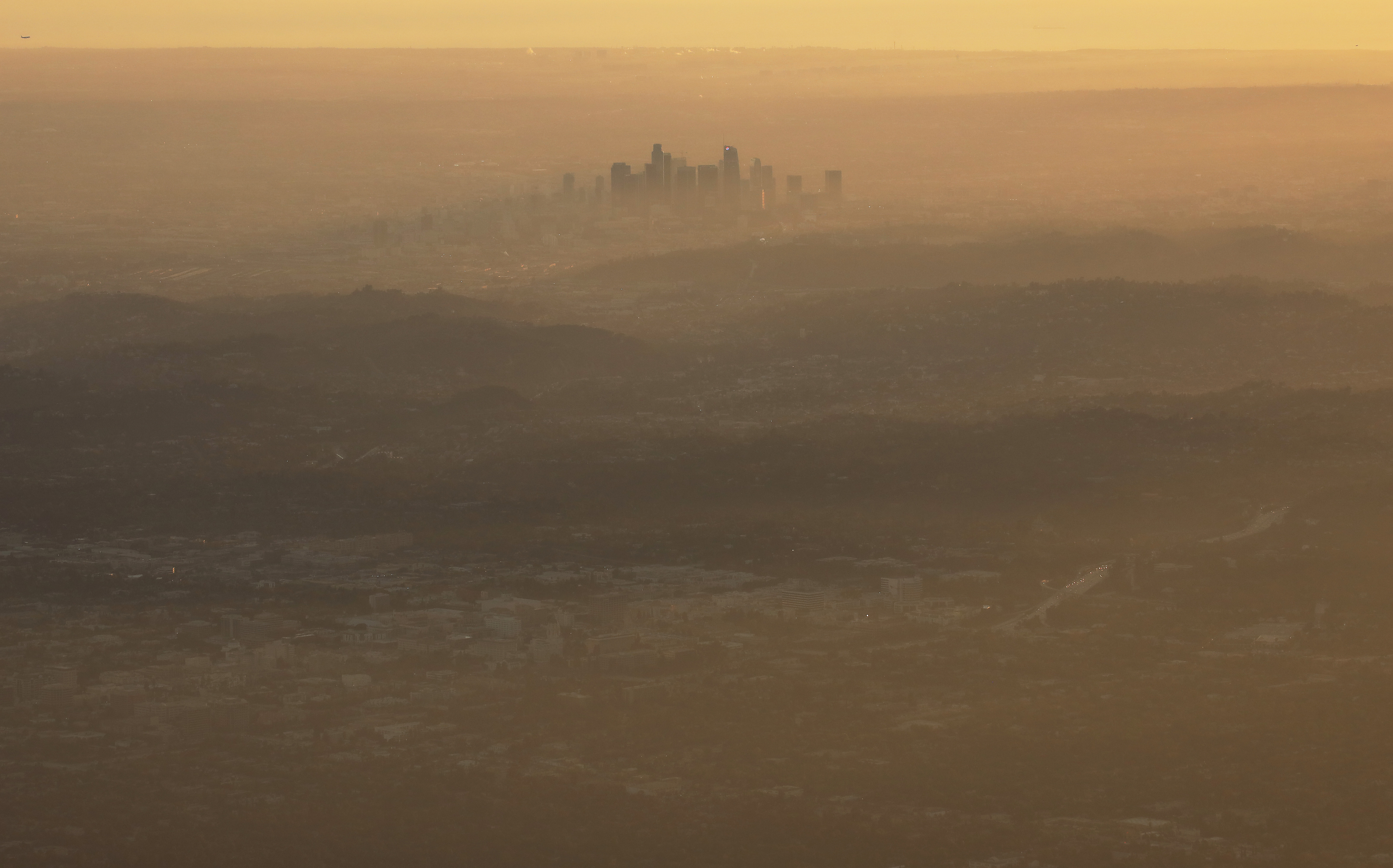 """PASADENA, CALIFORNIA - NOVEMBER 05: The buildings of downtown Los Angeles are partially obscured in the late afternoon on November 5, 2019 as seen from Pasadena, California. The air quality for metropolitan Los Angeles was predicted to be """"unhealthy for sensitive groups"""" today by the South Coast Air Quality Management District."""