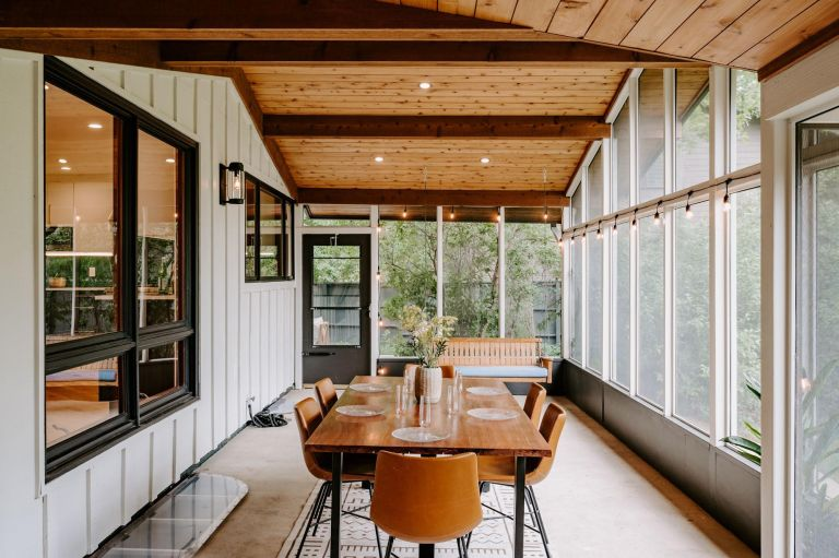 Wooden dining table with chairs in open sunroom/conservatory with a forest view and spot lighting