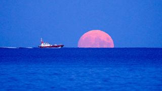 A pilot boat passes the rising Harvest Moon on September 20, 2021 off Swanpool Beach, Falmouth, England.