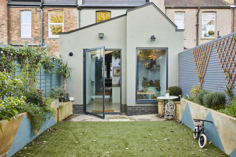 An exterior shot of the kitchen extension with angled roof and flower beds with blue painted triangles on the sides