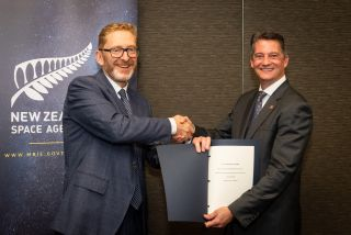 New Zealand Space Agency head Peter Crabtree and Kevin Cover, charge d'affaires at the U.S. Embassy in New Zealand, pose with a copy of the Artemis Accords.