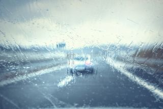 Abstract blurred vehicle dangerous highway driving in heavy rainfall. Stormy conditions on the highway. Blur effect visualizes the speed, poor vision and dynamics at high speed.