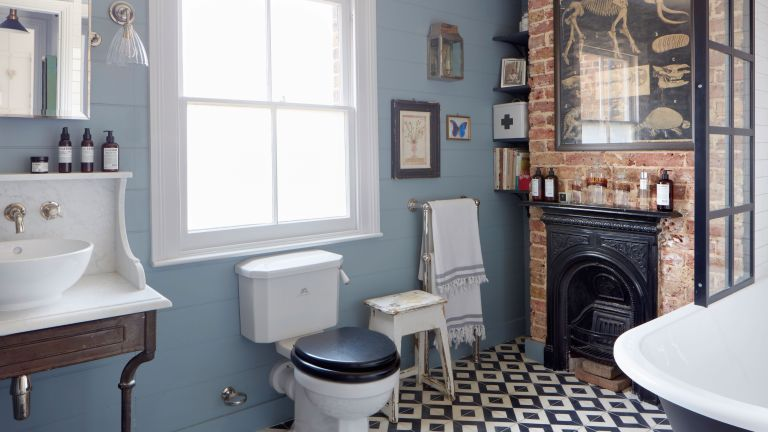 how to clean a toilet: traditional bathroom with patterned monochrome floor, light bluie walls and brick wall