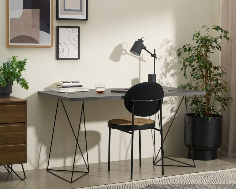 Made Solly Wide Desk with concrete-effect top and black legs, beside plant and with rattan chair