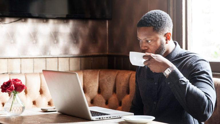 Man drinking a cup of coffee whilst working on a laptop