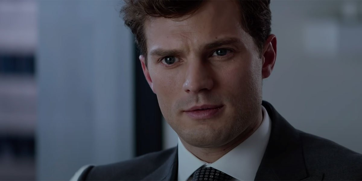 Jamie Dornan sitting in his office with a blue suit asking questions in Fifty Shades Of Grey trailer.