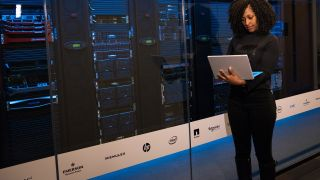 woman on laptop in front of data center