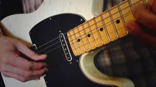Close-up of man playing Fender Telecaster electric guitar