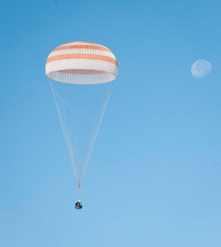 The Soyuz TMA-21 spacecraft is seen with the Moon in the background as it lands with Expedition 28 Commander Andrey Borisenko, and Flight Engineers Ron Garan and Alexander Samokutyaev in a remote area outside of the town of Zhezkazgan, Kazakhstan, on Frid