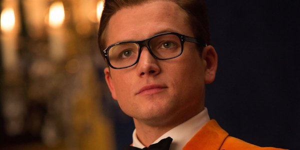 Kingsman: The Golden Circle Eggsy stoic pose in orange jacket
