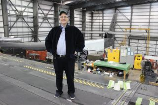 Stratolaunch Systems founder Paul G. Allen, billionaire tech entrepreneur and philanthropist, stands on the main wing of the massive Stratolaunch carrier aircraft designed to launch rockets into space. Allen died Oct. 15, 2018. He was 65.