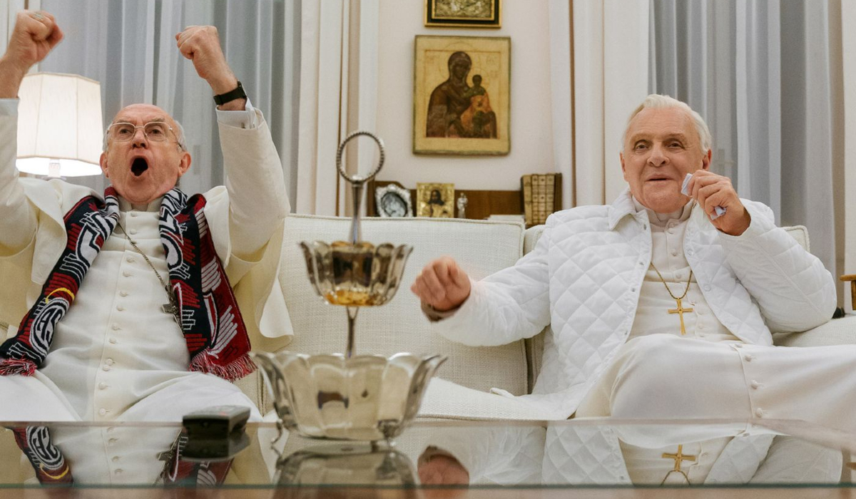 The Two Popes Jonathan Pryce and Anthony Hopkins watching TV on the couch
