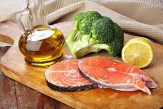 Salmon, olive oil, broccoli and lemon on a cutting board.