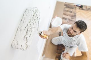 Man painting a wall when decorating