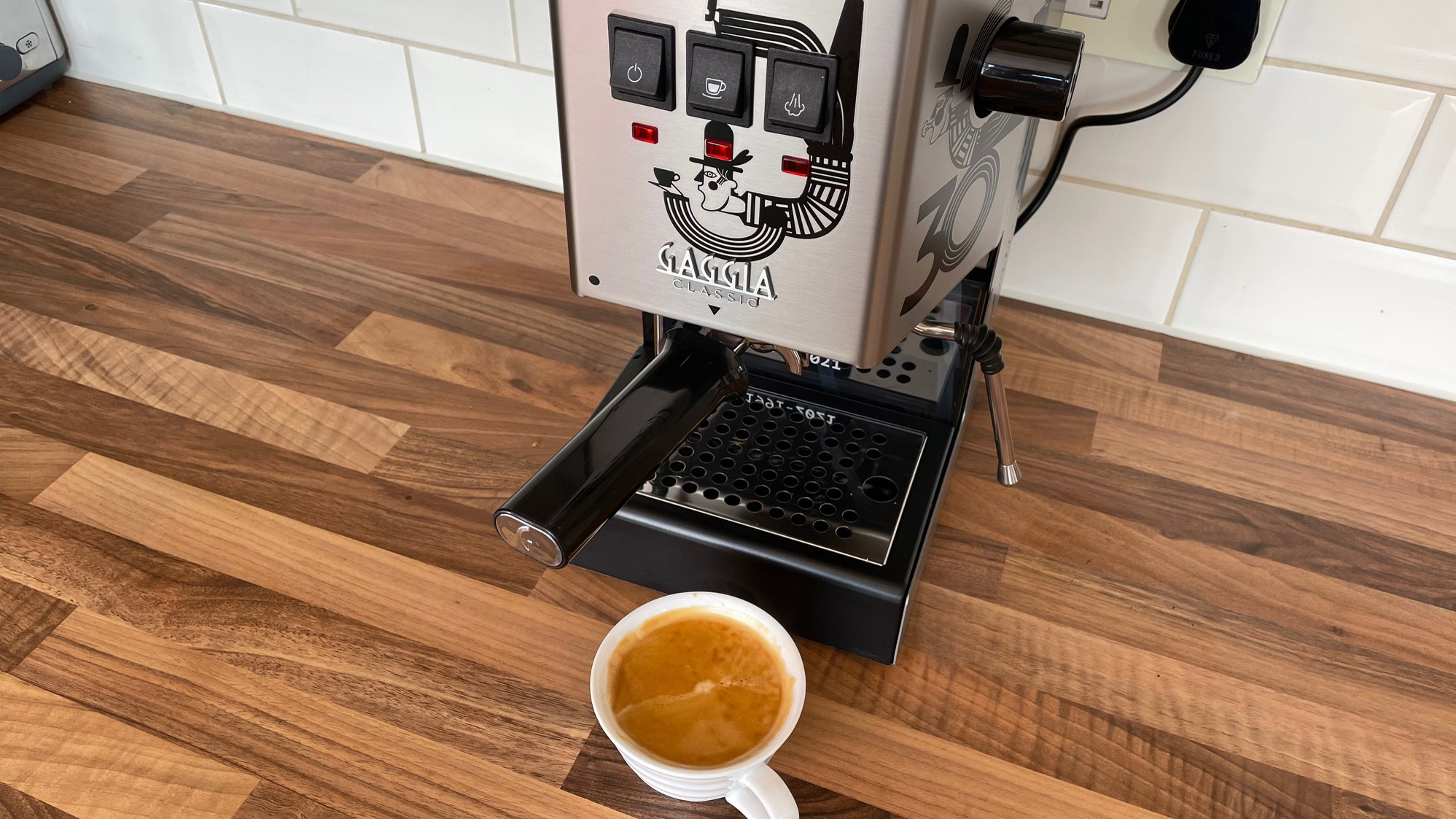 The Gaggia Classic on a kitchen countertop having just brewed an espresso