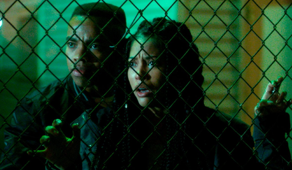 Joivan Wade and Lex Scott Davis concerned behind a chain link fence in The First Purge.