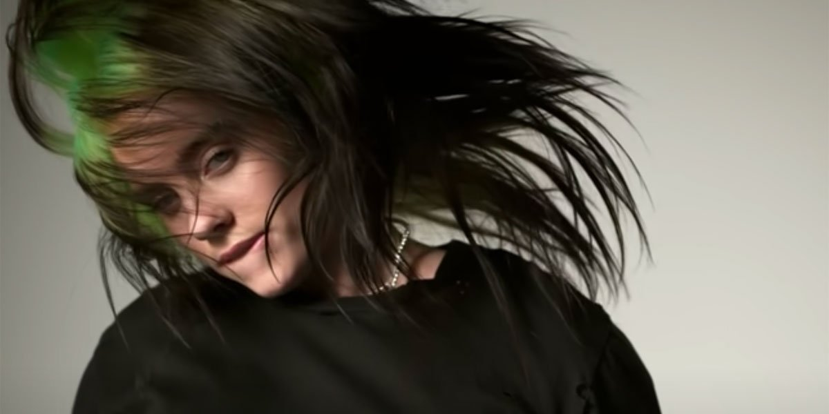 Billie Eilish screenshot from ilomilo video, jumping on trampoline green hair