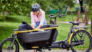 Woman settling baby in Raleigh Stride cargo e-bike