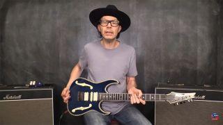 Paul Gilbert holding an Ibanez electric guitar