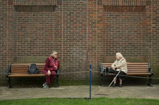 Two women keep 6 feet (1.8 meters) apart as they speak to each other from adjacent park benches amidst the novel coronavirus COVID-19 pandemic, in the centre of York, northern England on March 19, 2020.