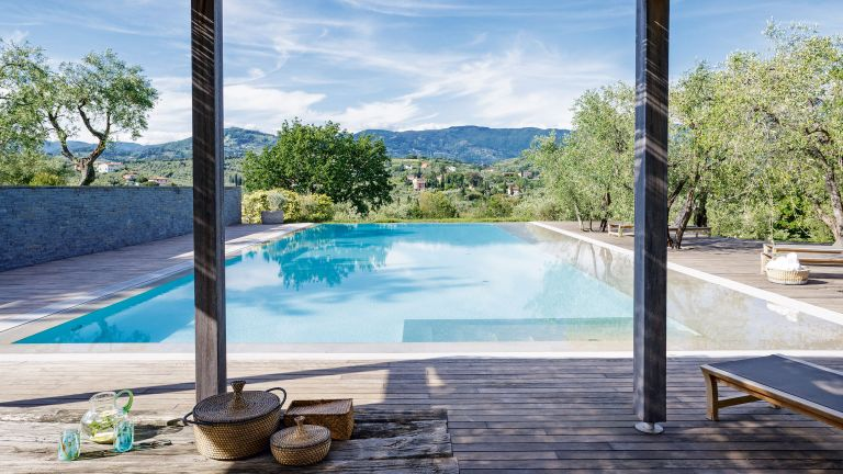 An example of pool ideas showing a shaded pergola area looking out onto a pool surrounded by olive groves