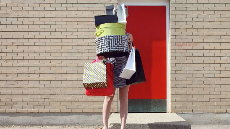 Woman in high heels and a dress juggles shopping bags and boxes stacked high above her head.