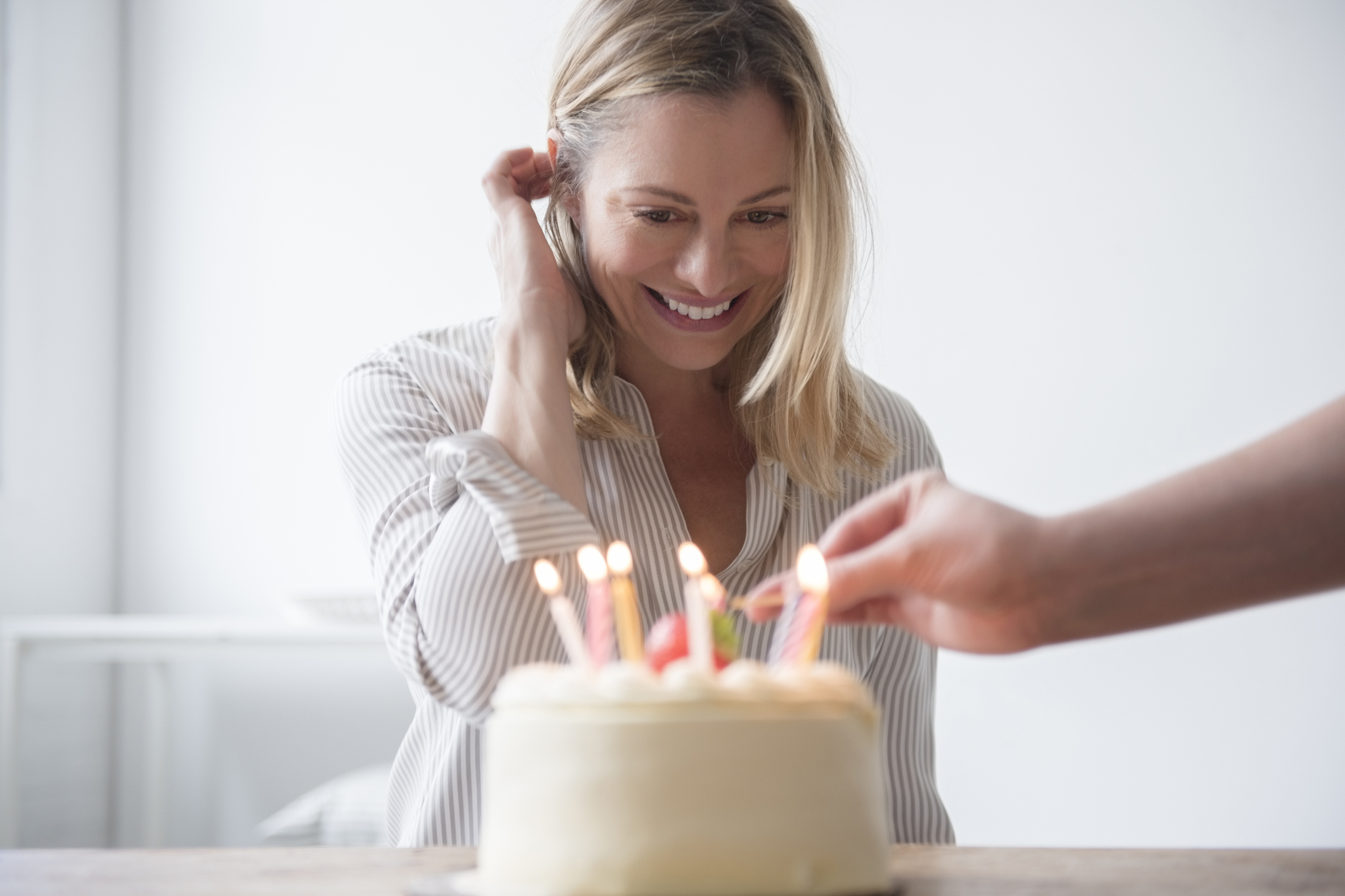 Friend lighting candles on cake as 50th birthday gift idea for woman