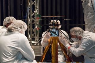 Mars Helicopter team members work the flight model (the vehicle going to Mars) in the Space Simulator, a 25-foot-wide (7.62 meters) vacuum chamber, at NASA's Jet Propulsion Laboratory in Pasadena, California.