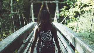 Photo of a woman walking over a scenic wooden bridge