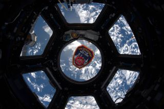 A New York City Fire Department patch floats in the Cupola window of the International Space Station on the 18th anniversary of the 9/11 terror attacks.
