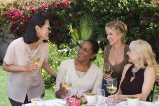 Middle-age women gather around a table, laughing and drinking wine